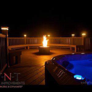 deck w/ seating, lighting, hot tub, & fireplace (nighttime)