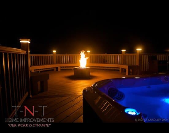 deck w/ seating, lighting, hot tub, & fireplace (nighttime)
