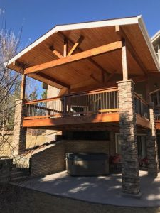 covered deck shingled roof stone pillars all covering a hot tub